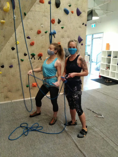 Two members with masks preparing to climb at Strait Up Climbing