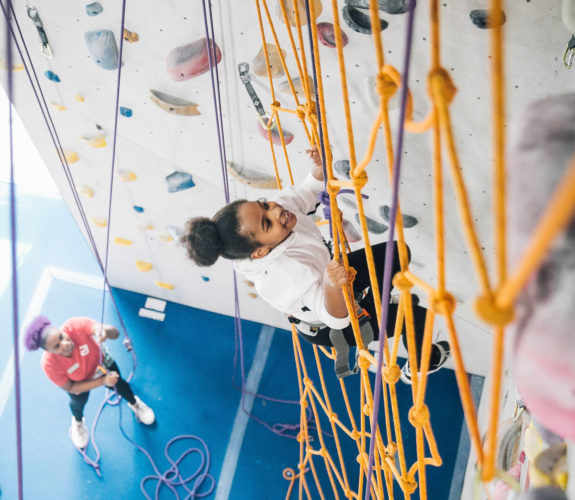 Summer Youth Program Marketing - a summer camper climbs the ropes at The Cliffs.